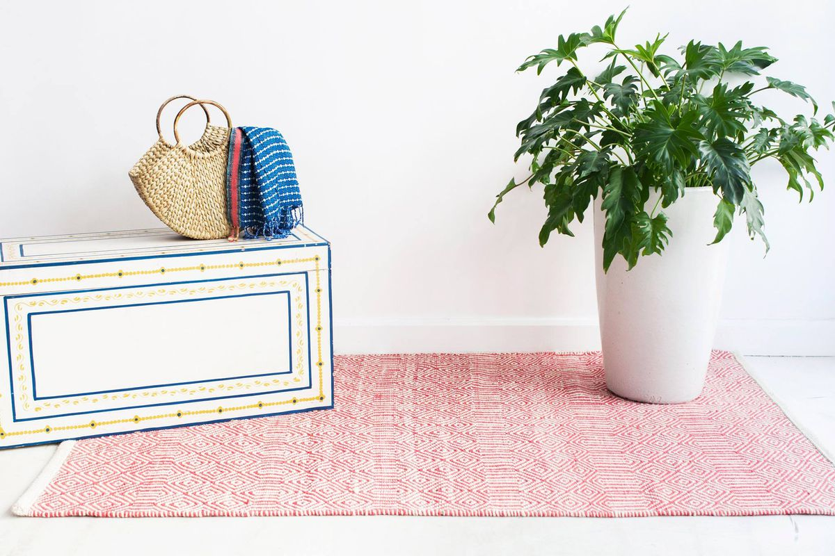 A woven tote bag on a trunk, filled with a towel