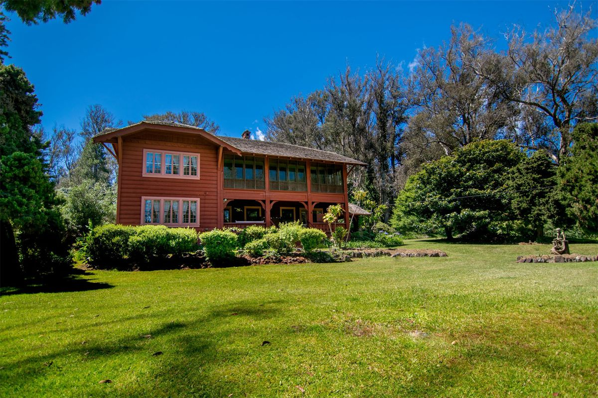 A large two-story red-framed lodge-style house with verandas on grassy lot surrounded by trees.