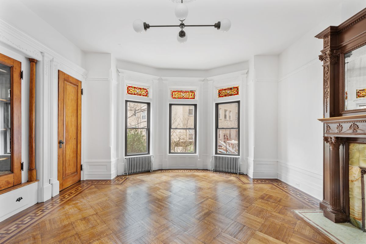 In a living room, three windows with pieces of stained glass on top, a fireplace, and parquet floors.