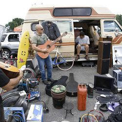 Caesar Barrios, center, attempts to sell a guitar, one of the many items for sale, while Gonzo Olea, right, repairs a piece of electronics Sunday at the Swap Meet in West Valley City. Olea and Barrios make a few extra dollars at the swap meet, which is held on Saturdays and Sundays.