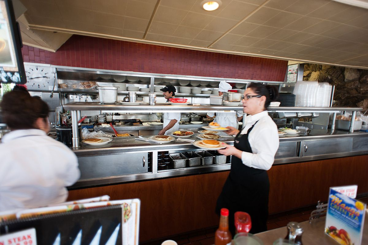 A worker inside of a restaurant carries plates and picks up more from the kitchen in a fast-paced environment.