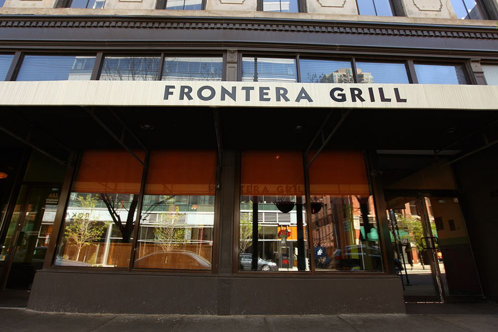 """The exterior of a restaurant from the street with large windows. An awning overhead reads """"Frontera Grill."""""""