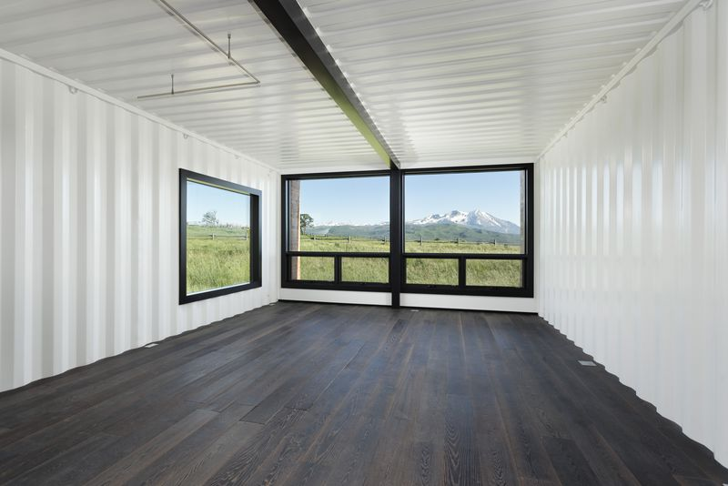 In a large room with white walls and dark brown floors, windows have mountain and grassland views.