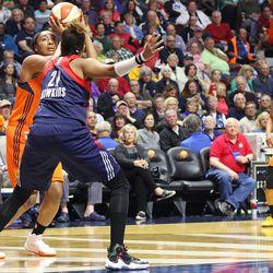 Connecticut Sun's Morgan Tuck (33) puts up a shot over Washington Mystics' Tianna Hawkins (21).