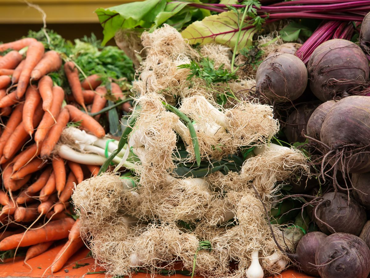 Carrots, scallions, and beets on display at a farmers market.