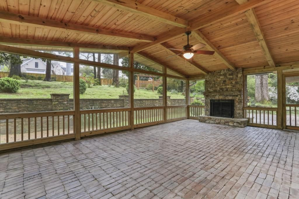 A huge screened-in porch with a ceiling fan overhead.