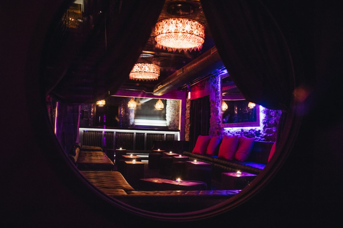 dark lounge with chandeliers and candles