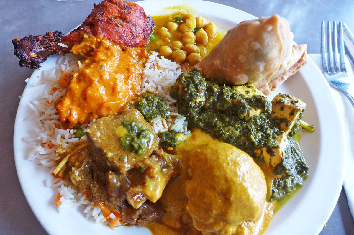 A plate of Indian food, including a tandoori drumstick, saag paneer, and a samosa, among other dishes
