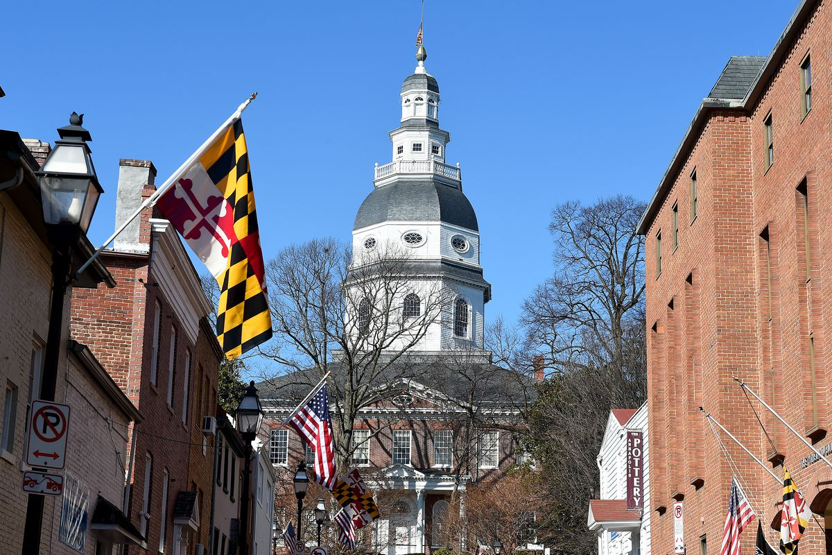 The Maryland State House building is pictured. In the foreground is a Maryland state flag.