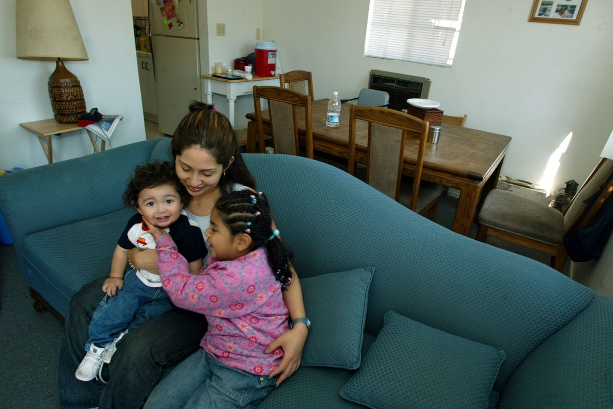 A woman sits on a couch in her home with her two small children.