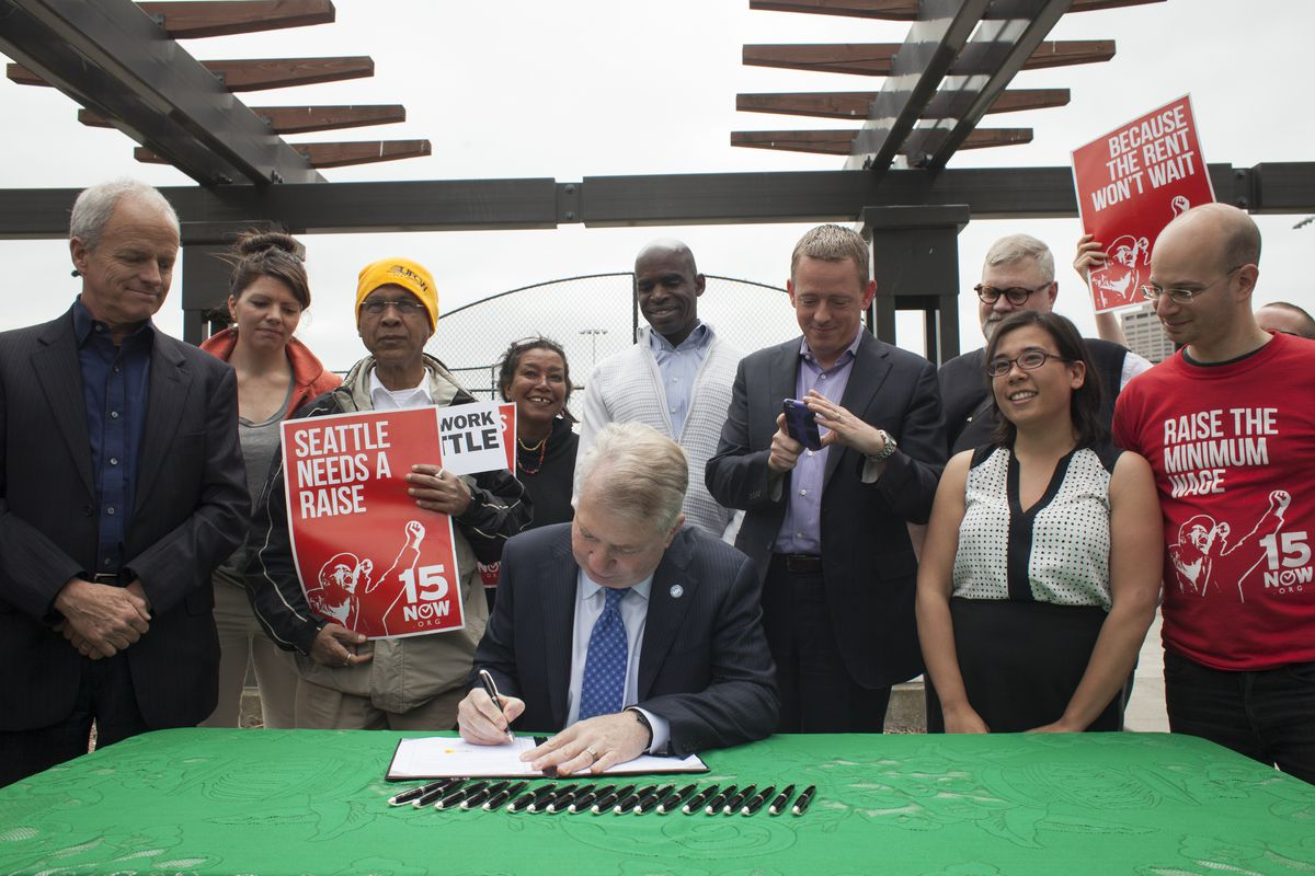 Seattle mayor Ed Murray, with city council members, signs minimum wage increase