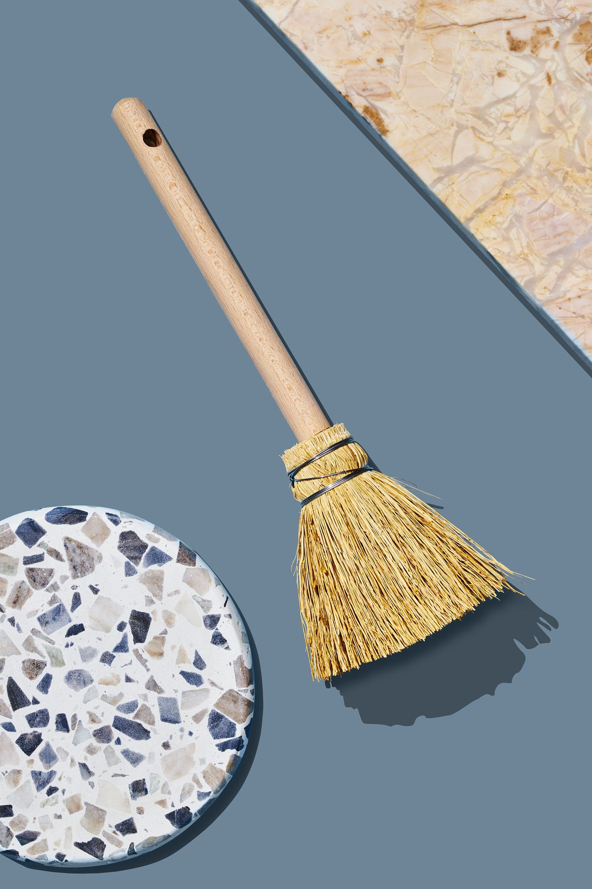 A small straw whisk broom which is part of the Curbed Holiday Gift Guide 2019. The broom is laying on a blue flat surface and is flanked by various design objects.