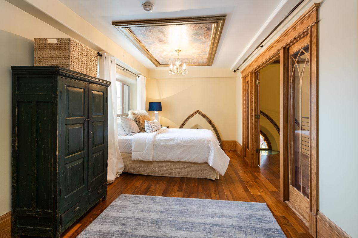 A long narrow room with wooden floors and a black closet has a white bed.