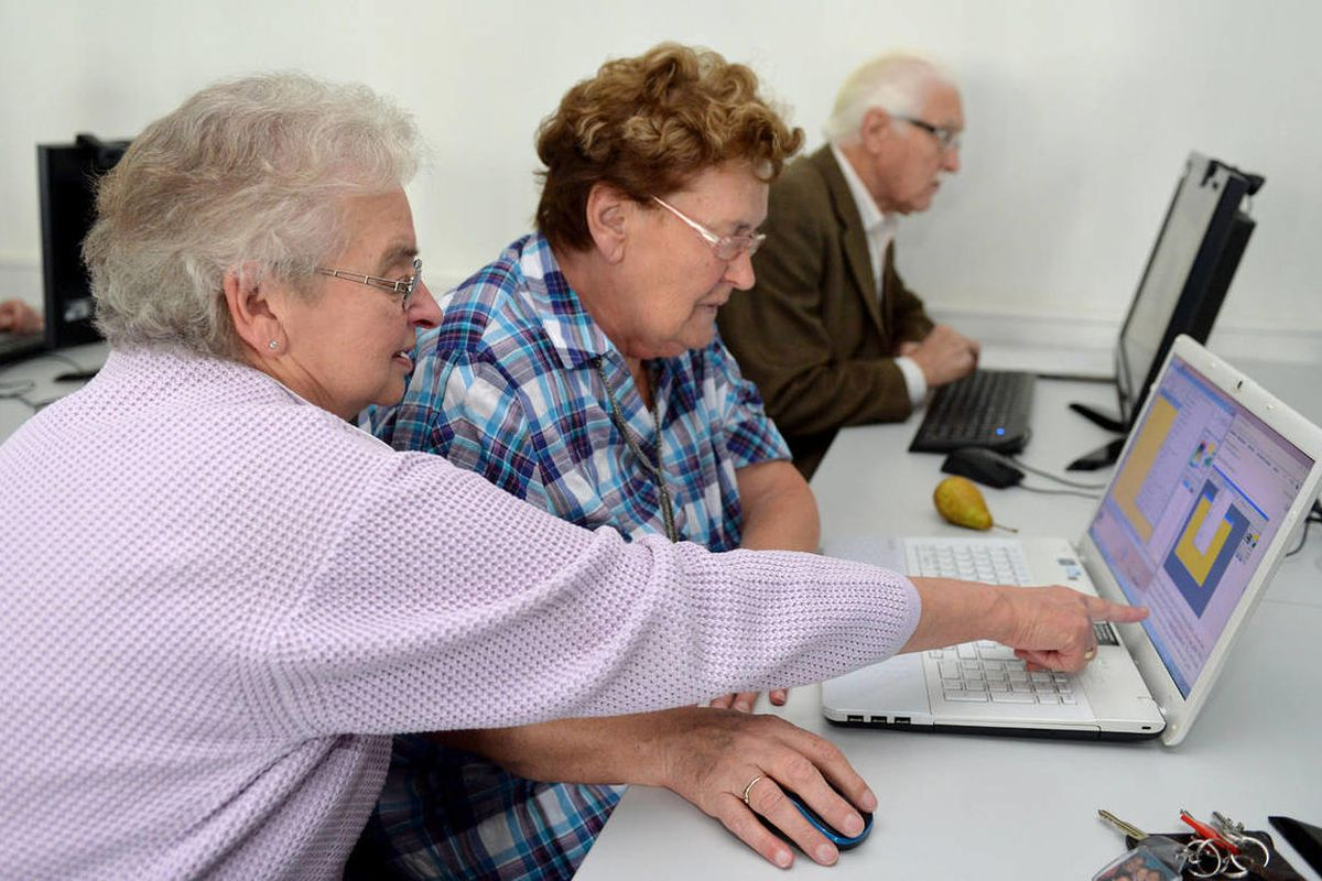 Instructor Johanna Zurborg (75, L) explains a software application on a notebook to Maria Hohnorst (72) during the internet cafe for senior citizens at the adult education centre in Vechta, Germany, 27 September 2013.