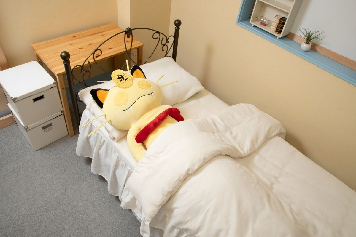 A Gigantimax Meowth plush toy resting in bed