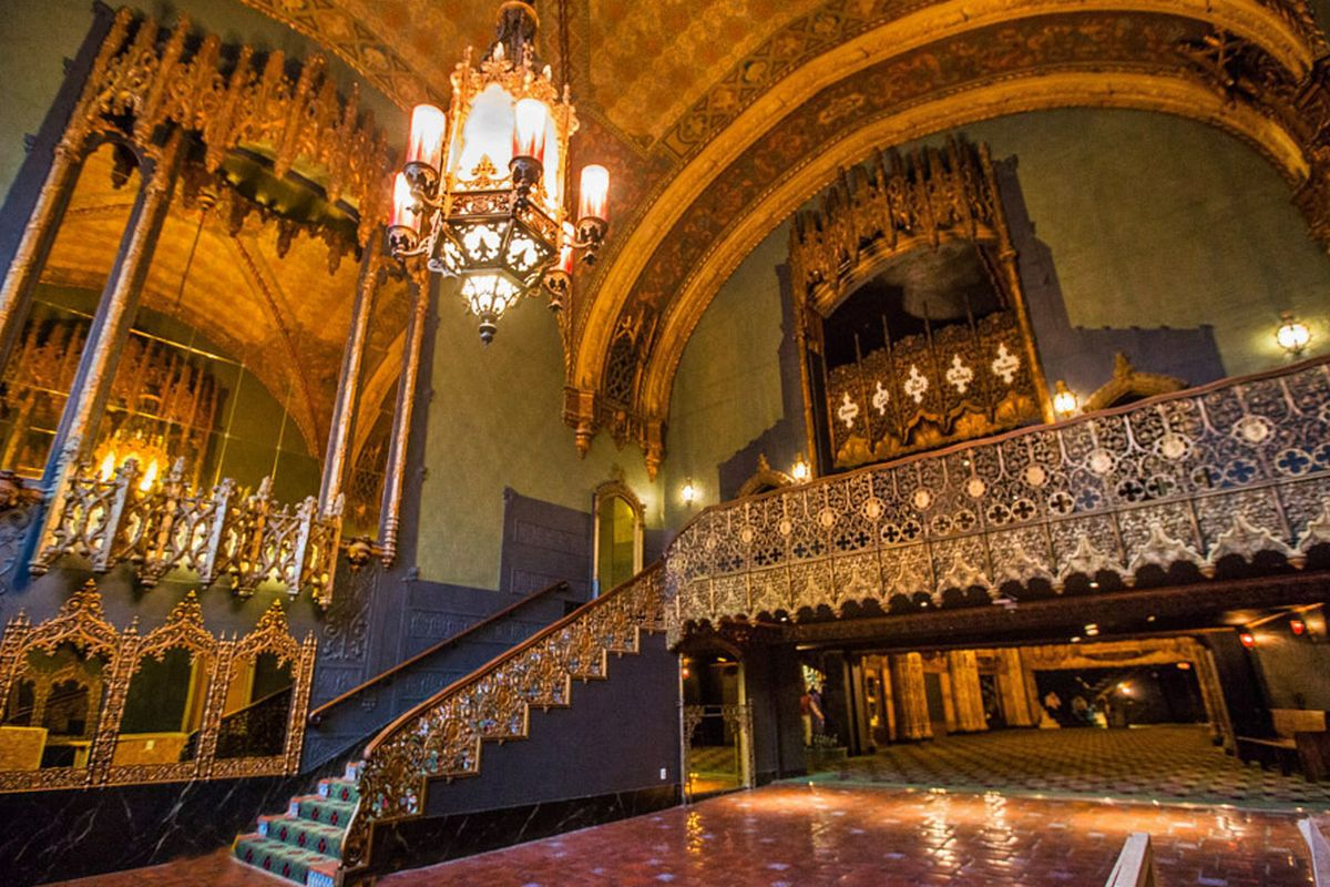 The interior of the Theatre at Ace in Los Angeles. There is a staircase and bannister that has elaborate metalwork. There is a large chandelier hanging from the ceiling. Arches with metalwork are on the walls.