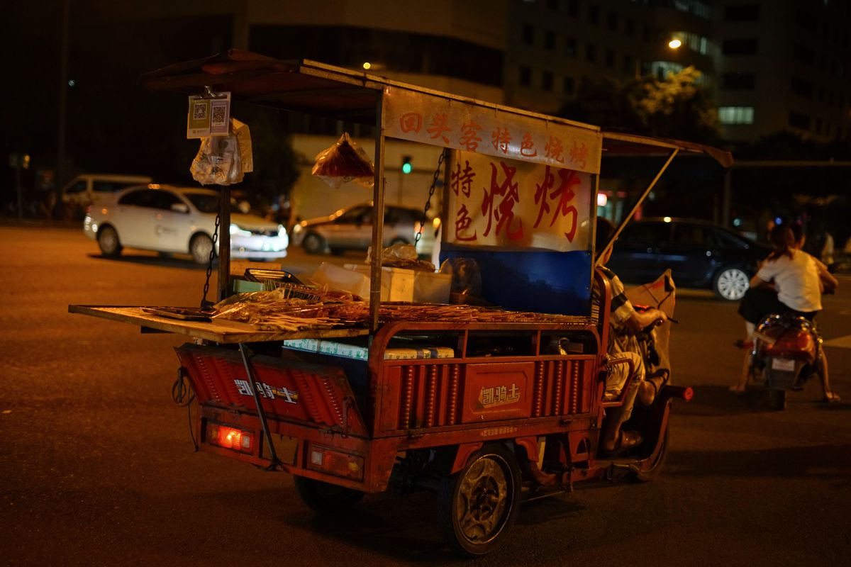 A small food cart is being driven down the street.