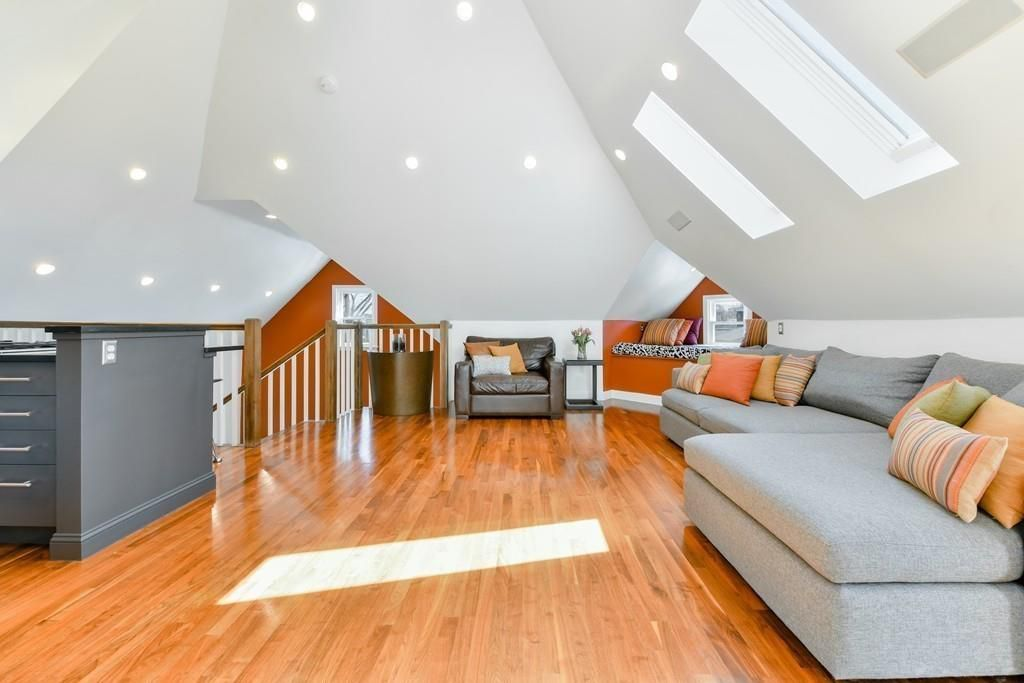 That loft, with peaked ceilings, a long couch, and skylights.