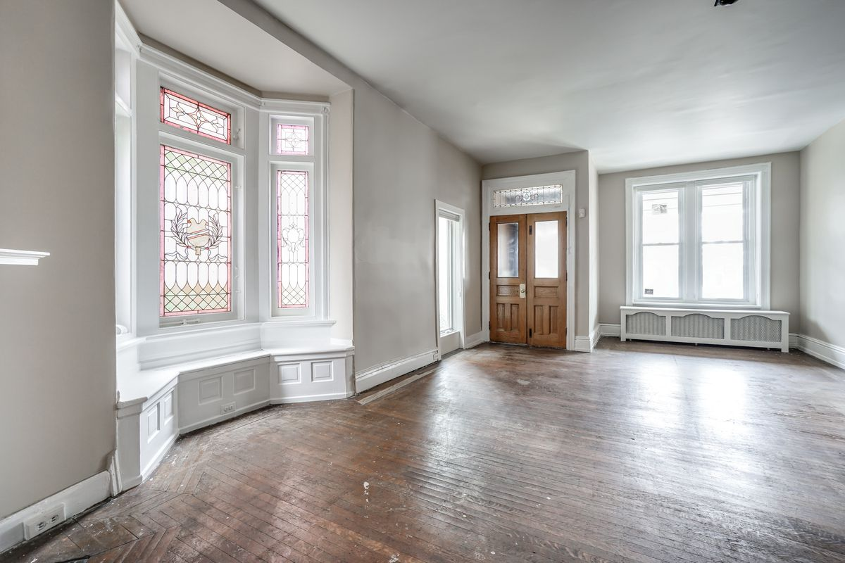 A spacious living room with hardwood floors, a bay window with stained glass windows.