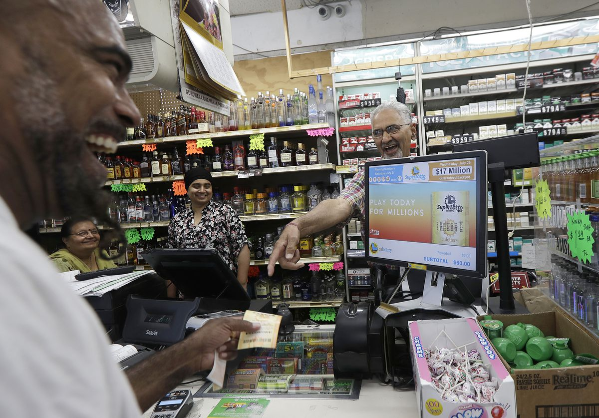 Mike Bostic, left, smiles as he is handed a lottery ticket by owner Kewal Sachdev at Ernie's Liquors in San Jose, Calif. July 25, 2018. The state lottery's verified Twitter feed says the winning ticket, worth more than $500 million, was sold at Ernie's Li