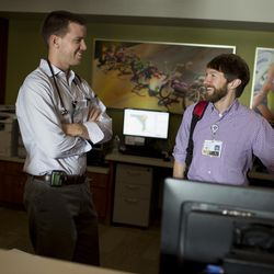 Doctors Ryan Taylor, left, and Anthony Zabel laugh as they do hospital rounds Thursday, April 28, 2016, at Franciscan St. Francis Hospital in Indianapolis. Taylor and Zabel are both pediatric residents at the hospital.