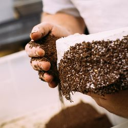 Real chocolate sprinkles are patted onto the cake's sides.