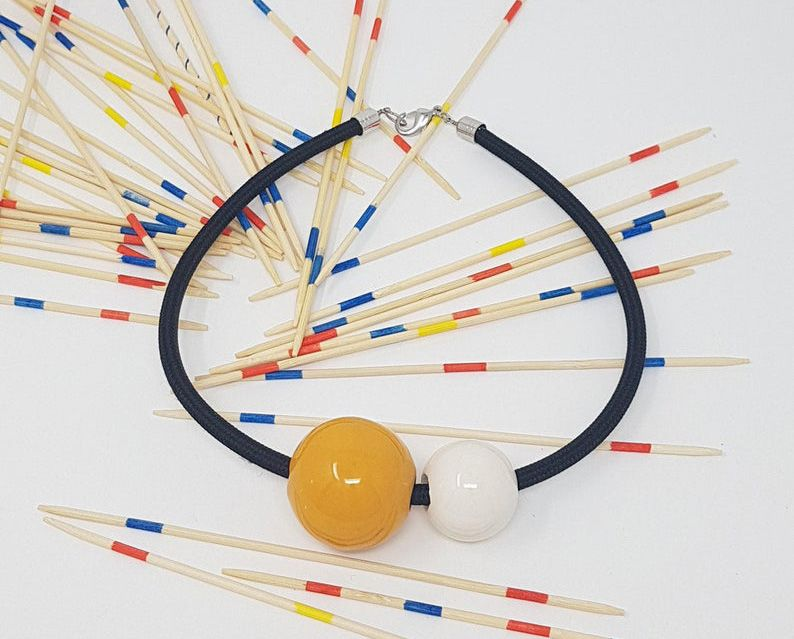 A black cord with a yellow ceramic ball and a smaller white ball.
