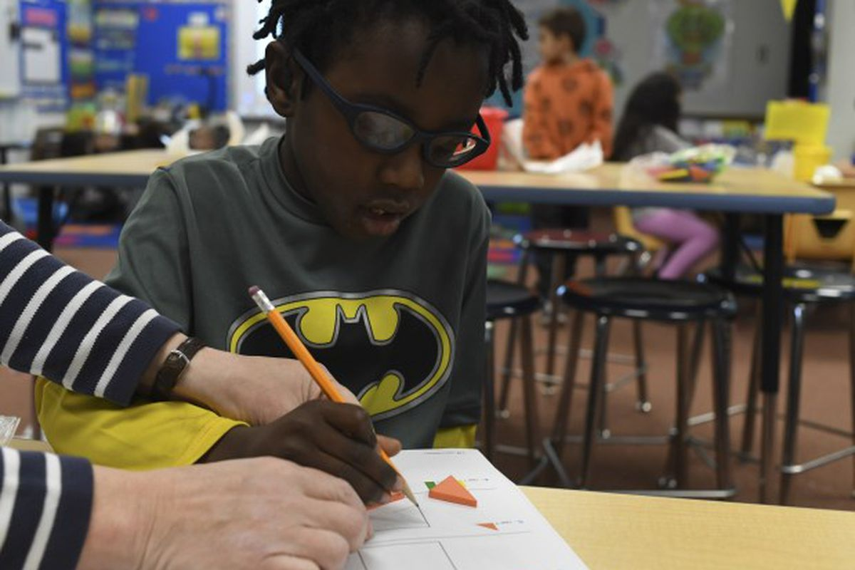 Tyree Howard, 5, gets help with his shapes during kindergarten class at Westgate Elementary School in Lakewood, Colorado.
