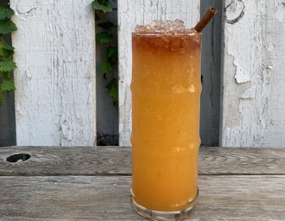 An orange cocktail in a tall narrow glass.