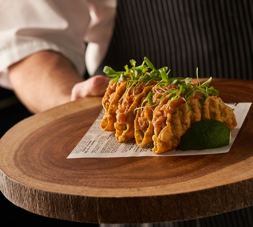A person holding a platter of spicy tuna tacos.