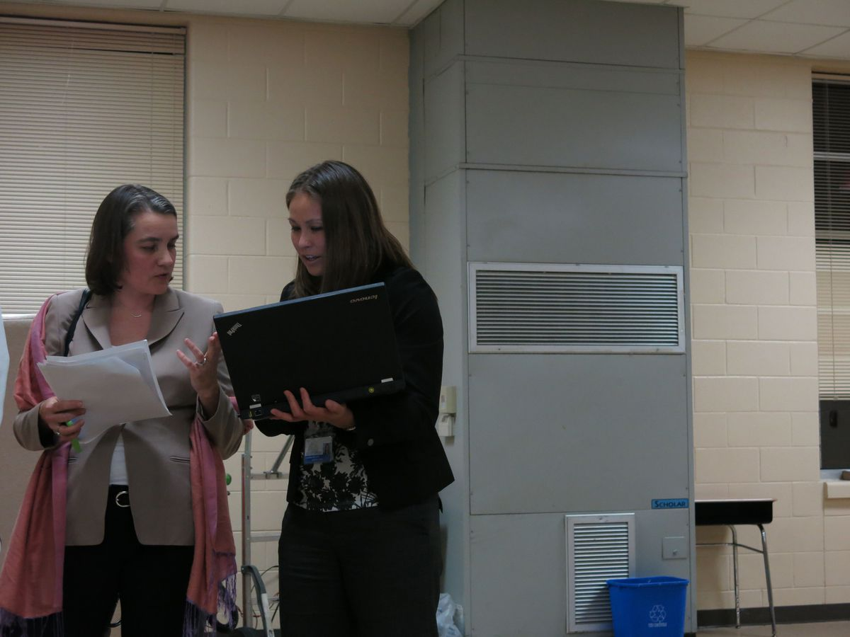 Board member Amy Frogge and an ASD official discuss data on the sidelines of the meeting.