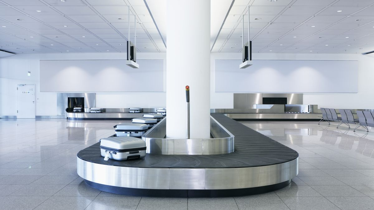 A luggage carousel at an airport with identical silver bags, no people.