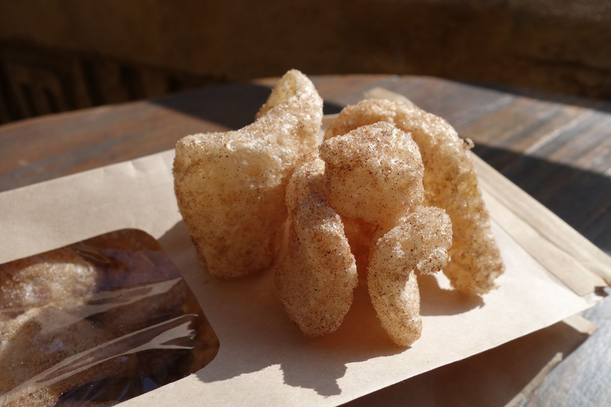 A handful of puffy pork rinds sitting on the brown paper packaging they arrive in