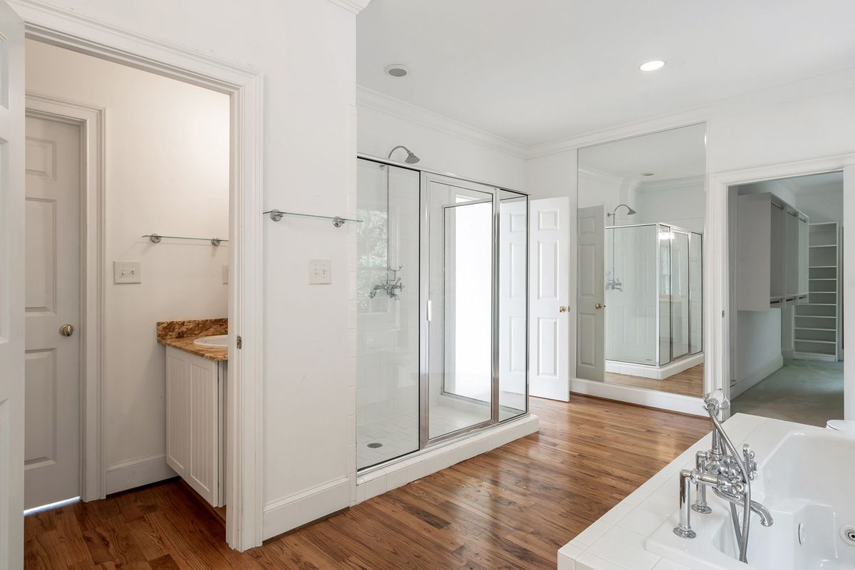 A huge white master bathroom with a large mirror.