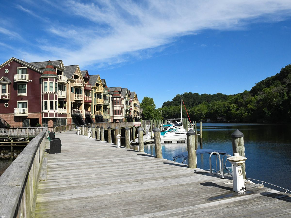 A boat dock, with buildings in the background, under blue skies.