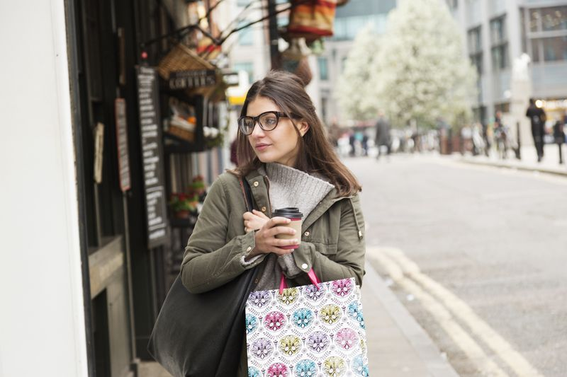 Woman in glasses holding a coffee and a patterned shopping bag.