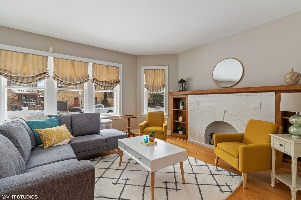 The living room gets lots of light from the large bay windows and has a decorative fireplace. There is a sectional couch and two yellow armchairs.