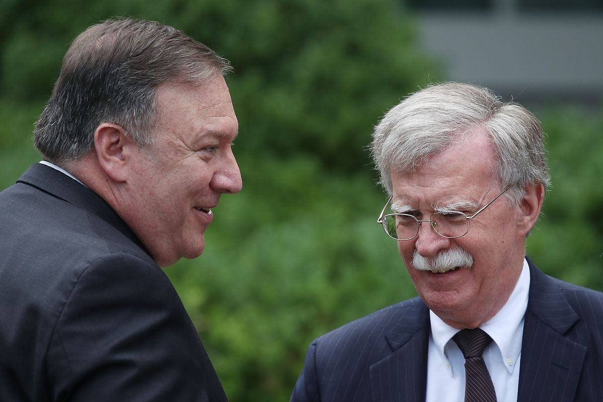 Secretary of State Mike Pompeo talks with National Security Adviser John Bolton before a news conference won June 7, 2018.