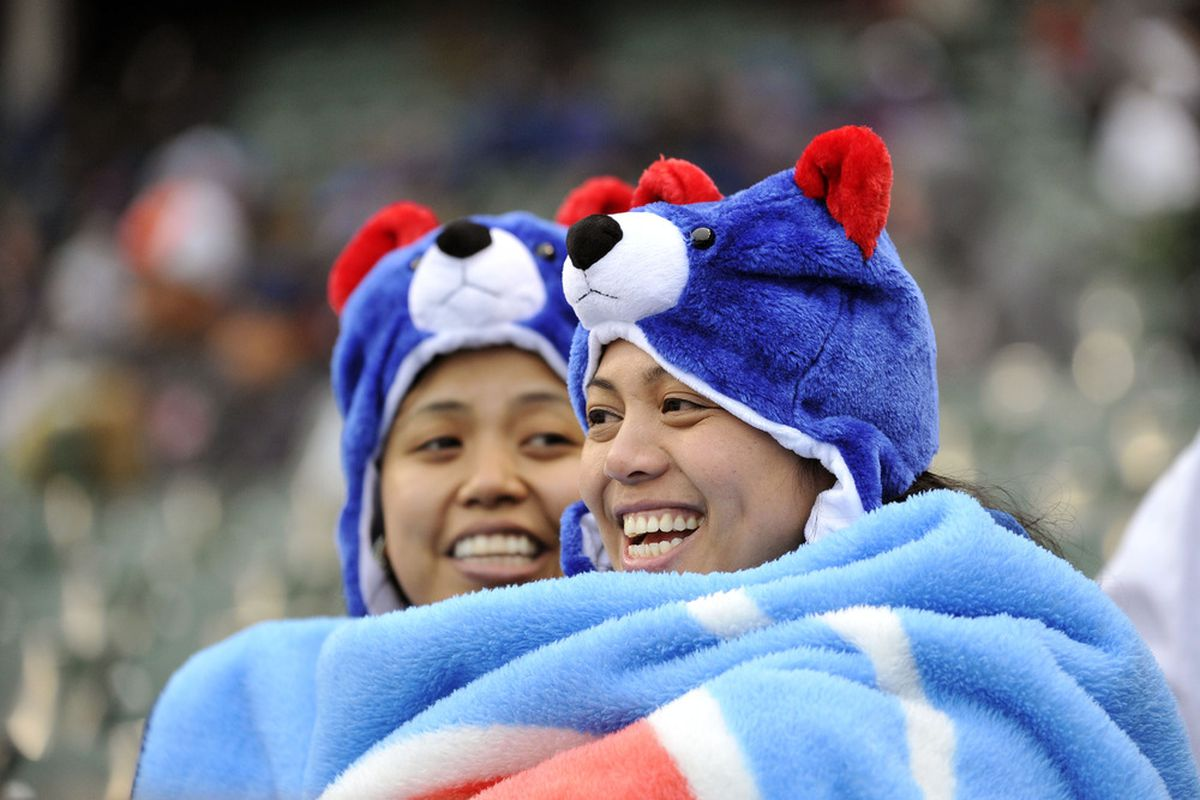 Pam Aceron (R) and Sha Melo try and stay warm during the Chicago Cubs Cincinnati Reds game at Wrigley Field in Chicago, Illinois. The Reds defeated the Cubs 9-4.  (Photo by Brian Kersey/Getty Images)
