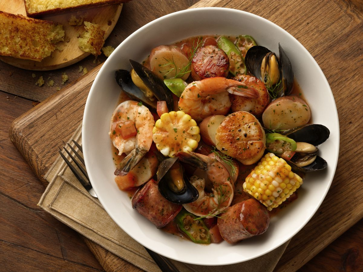 Overhead view of a white bowl full of sausage, pieces of corn on the cob, mussels, and shrimp