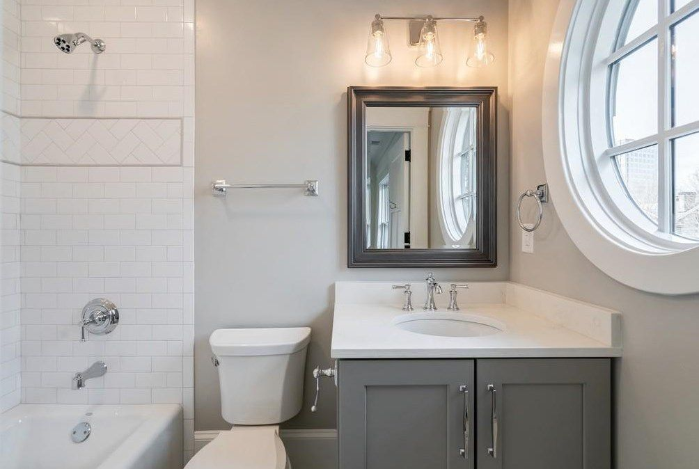 A white bathroom with a circular window at right.