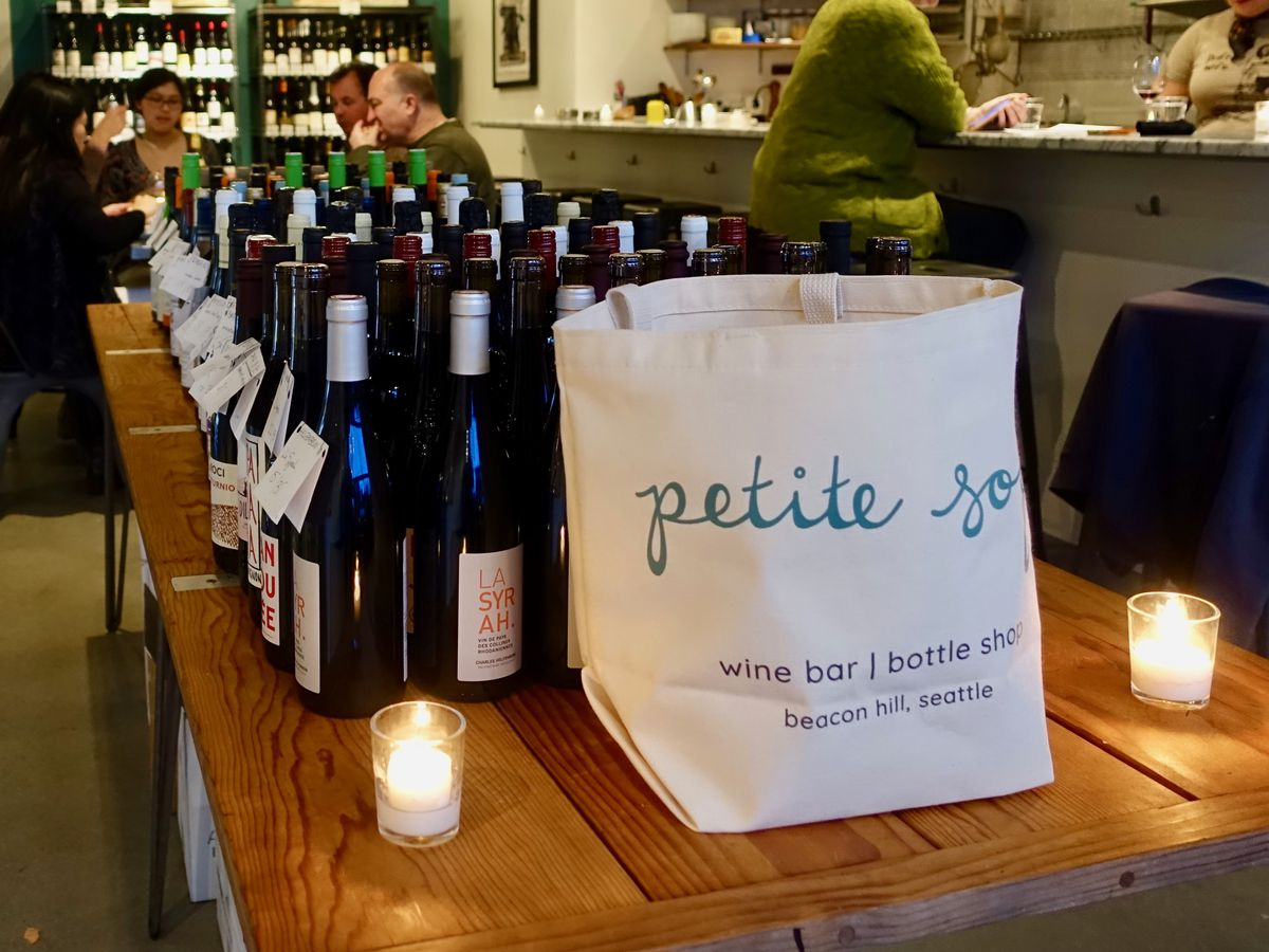 A group of bottles sit on a table next to a Petite Soif bag.