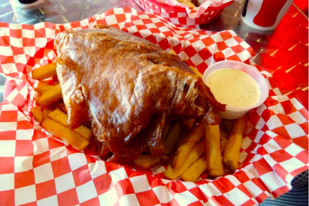 A piece of brown-crusted, glistening fried fish sits on a bed of fries, cradled in a red-and-white-paper-lined basket