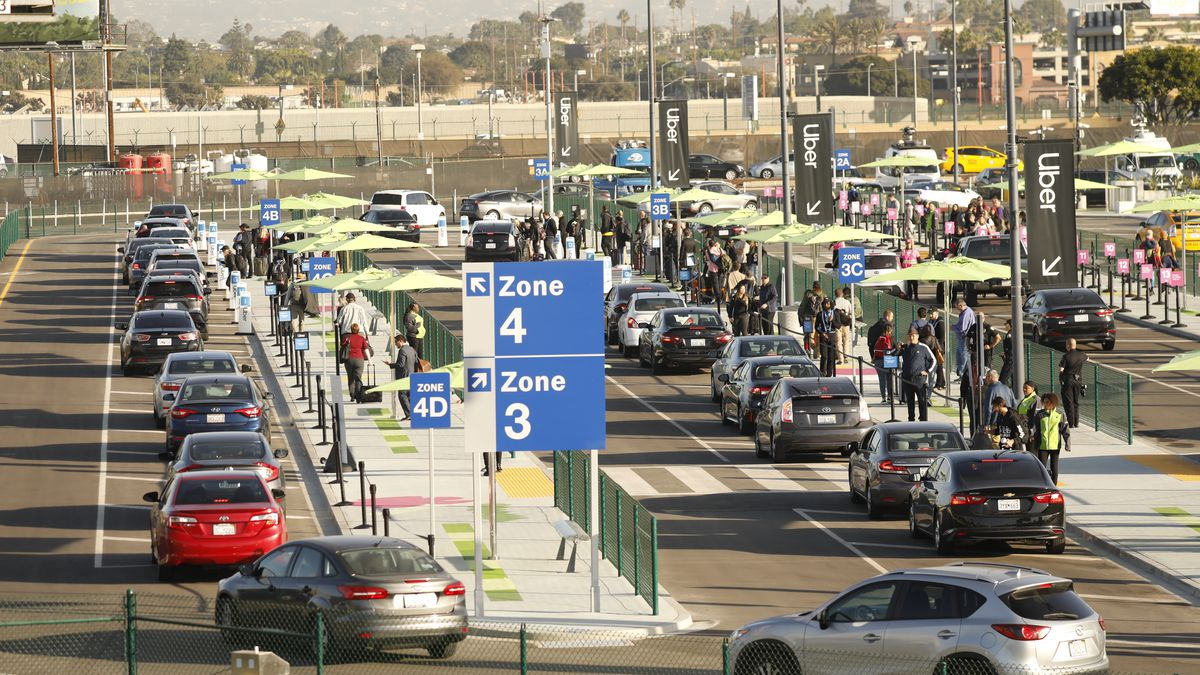 Rows of cars are lined up at an airport pickup parking lot with people holding luggage standing in long lines to access them. Signs that say Uber are seen in the background.