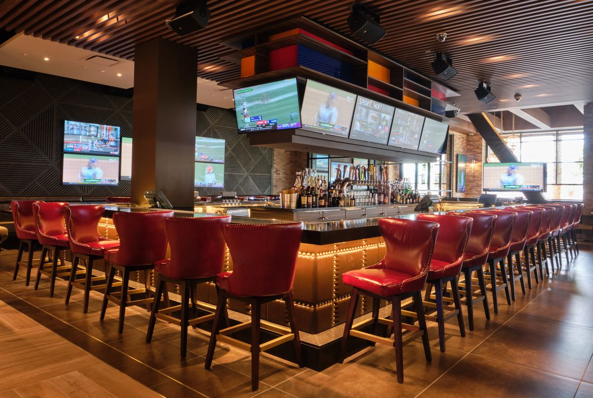 A center bar with TVs around the top and red leather stools