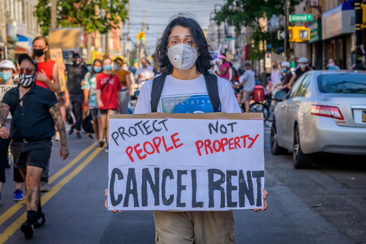 """A protester walking down a street carries a sign that reads, """"Protect people not property. Cancel rent."""""""