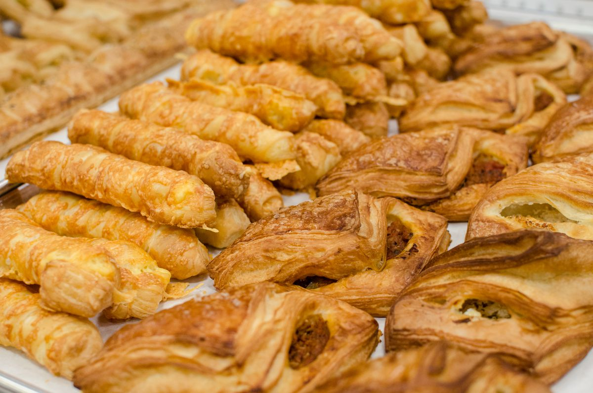 Tray full of two types of puff pastries: fat sticks with bubbly cheese on the outside and flaky triangles stuffed with a red paste-like filling