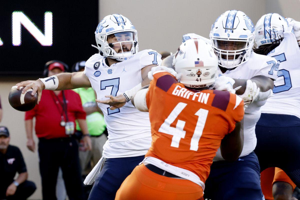 North Carolina Tar Heels quarterback Sam Howell throws a pass as offensive lineman Jordan Tucker holds back Virginia Tech Hokies defensive lineman Jaylen Griffin during the second quarter at Lane Stadium.