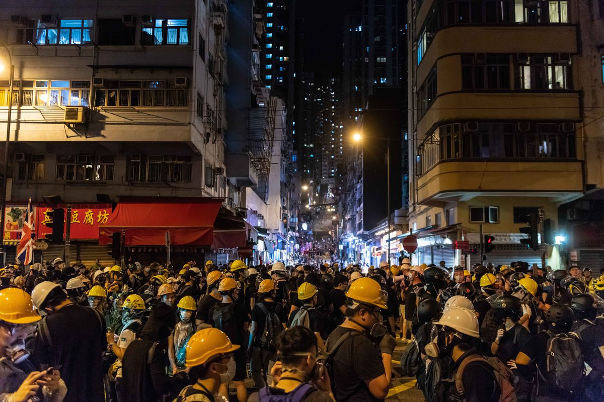 Protesters wearing hard hats fill a nighttime street in Hong Kong.