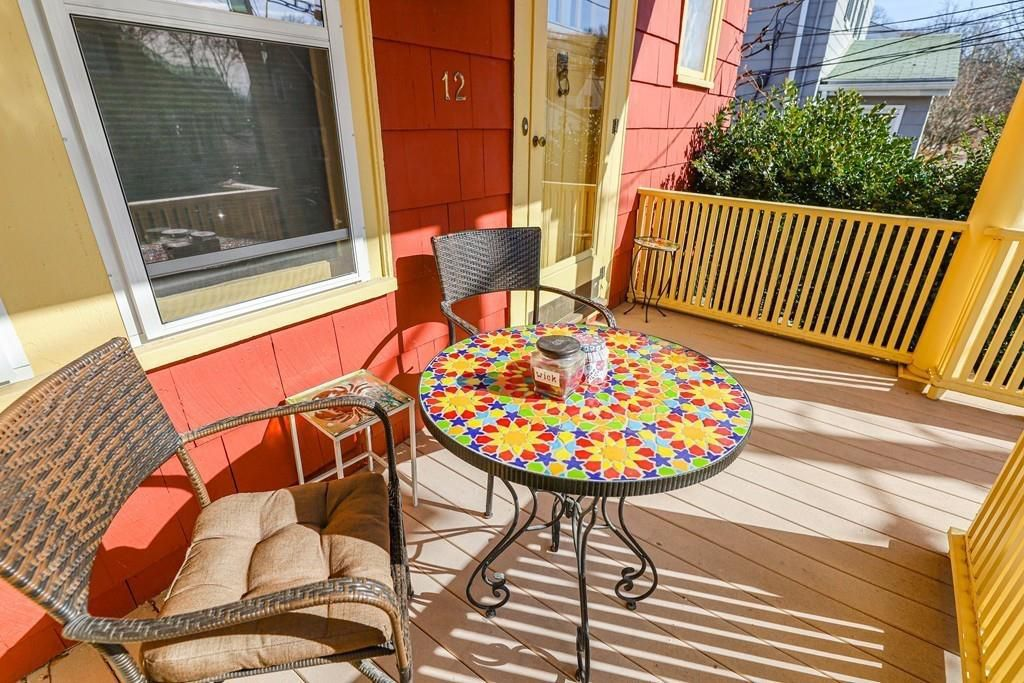A small back deck with two chairs on either side of a colorful table.
